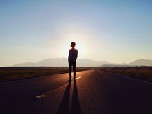 silhouette of a man standing in the center of a road