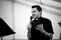 Priest speaking into microphone.