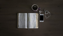 An open Bible, cup of coffee and cell phone on a table.