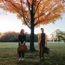 Couple carrying luggage through the park with fall foliage.