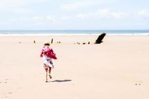 a girl running on a beach