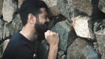 upset man pounding his fists against a stone wall