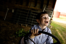 happy boy child with his hands on a tractor steering wheel