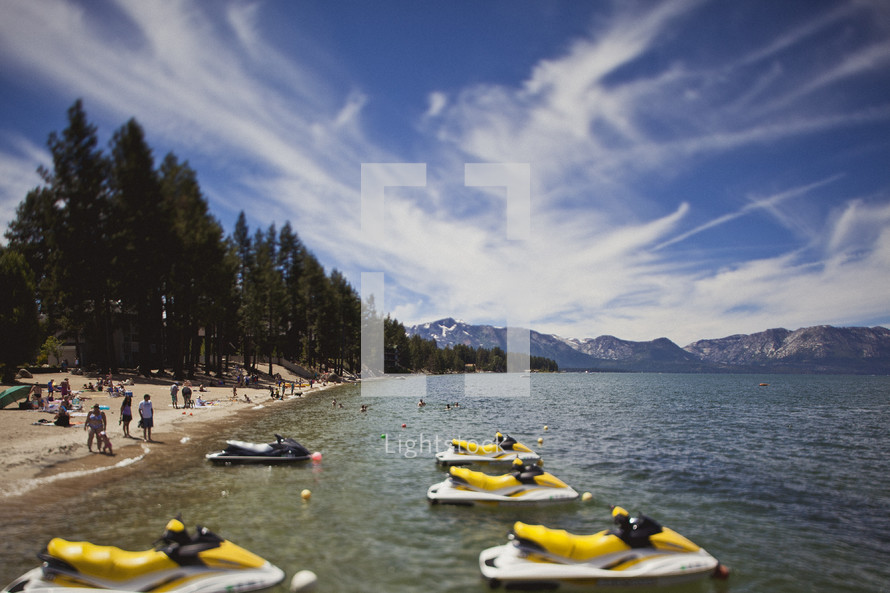 A beach with yellow jet skis tied in the water