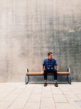 man waiting sitting on a bench