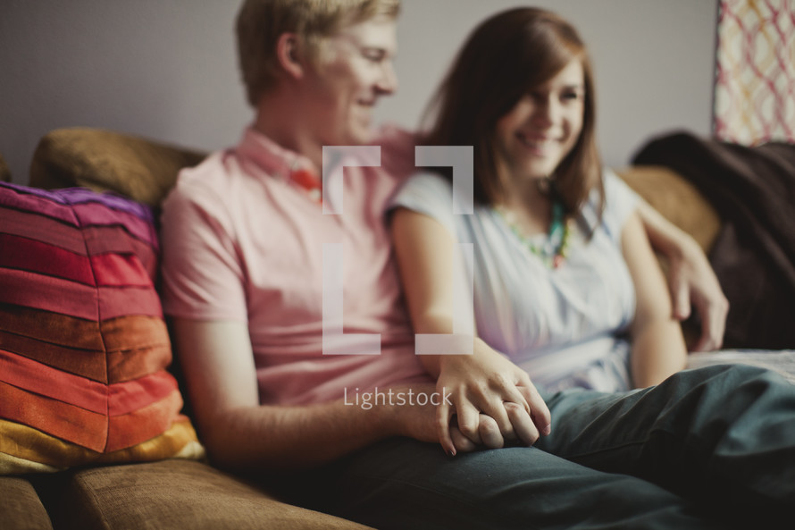 Couple sitting on couch holding hands