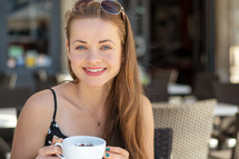 a smiling woman holding a coffee cup in the city