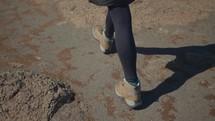 boots walking across a barren landscape