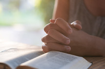 praying hands beside of a Bible