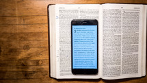 cellphone with Bible app and open Bibles
