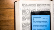 cellphone opened to a Bible app and an open Bible
