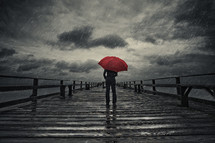 man standing on a pier in the rain with a red umbrella