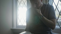man reading a Bible sitting at a window
