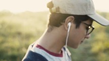 man listening to earbuds outdoors