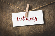 word testimony on white card stock hanging from a clothespin on a clothesline