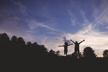 silhouettes of children jumping outdoors