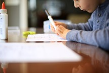 child doing school work with a marker