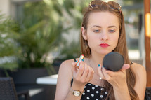 a woman putting on makeup outdoors