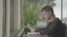 young man sitting at a window reading a Bible