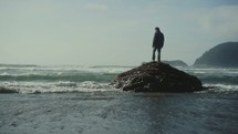 man watching the tide roll onto a shore