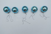 "A row of vintage blue Christmas ornaments with the word ""merry"" written with string."