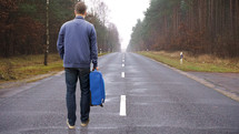 a man with a suitcase standing in the middle of a road