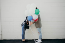 a couple kissing behind balloons