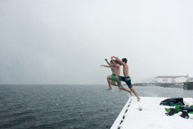 Three teens jumping from a snow covered bank into the ocean.