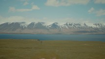 snow capped mountains, plains, and river
