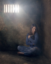 a woman sitting alone in a cell grasping a Bible