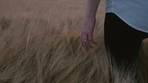 man walking through a field of tall grasses