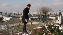 a man with a rose visiting a grave