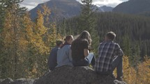 youth sitting on a rock outdoors in fall