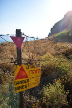 A barbed wire fence with a danger sign.