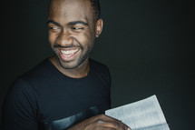 man smiling holding an open Bible