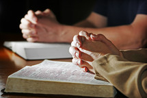A woman and man fold their hands in prayer over their Holy Bibles - This can represent a devotion time for a couple or a couple being part of a larger bible study, prayer group, or small group from church.