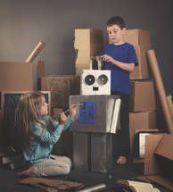 kids making a robot out of cardboard boxes