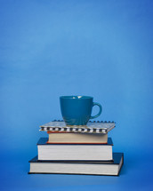 blue coffee cup on a stack of books