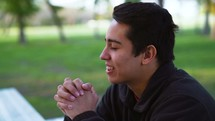 a man sitting at a picnic table praying