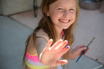 a little girl holding her hand out with paint on it