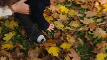 feet of a toddler boy in fall leaves