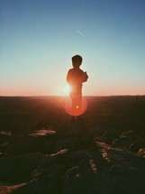 A silhouette of a young boy standing at the top of a mountain under intense sunlight.