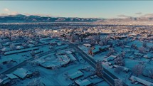 Aerial View Flying Over Snow-Covered Town With Mountains In Distance