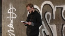 man reading a Bible standing in front of a graffiti covered wall