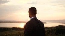 groom standing outdoors at sunset
