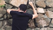 man pounding his fist against a stone wall