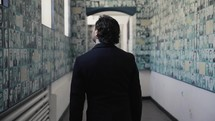 a man walking through the hallways of a museum
