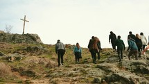 a group of people walking up a mountainside towards a cross