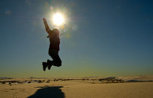 Silhouette of a person jumping off the ground on a sunny day.
