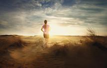 woman jogging on sand dunes at sunrise